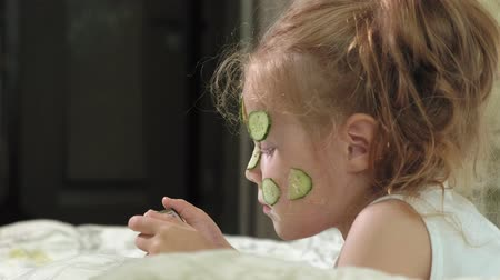 uses : A little beautiful girl cheerfully makes a cucumber masks at home and uses a smartphone Stock Footage