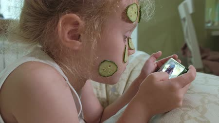toalha : A little beautiful girl cheerfully makes a cucumber masks at home and uses a smartphone Stock Footage