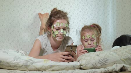 во : A woman with her daughter makes fun of cucumber masks at home