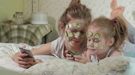 pepinos : A woman with her daughter makes fun of cucumber masks at home