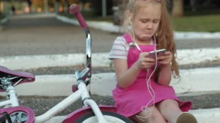enjoys : A little beautiful girl in a pink dress is sitting in the park on the steps and enjoys a smartphone in headphones, the bicycle is lying next to each other