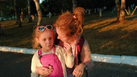 lépések : Mom and her daughter ride in a park on a bicycle and take a beautiful sunset