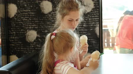 pace : A young mother and her little daughter spend time in a restaurant at a slow pace. Eating ice cream
