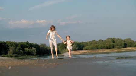 his : Close-up of mother and daughter playing together. A young mother is spinning his daughter at the beach of the sea shore super slow motion Stock Footage