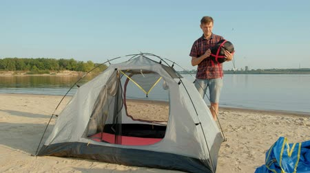 yakın : A mature man collects a tent on vacation outdoors near the sea Stok Video