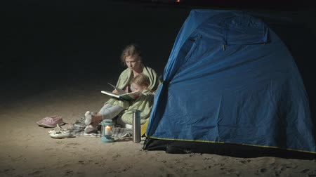 во : Mother and her beautiful daughter read a book near a tourist tent at night on the beach