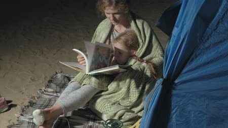 ukulele : Mother and her beautiful daughter read a book near a tourist tent at night on the beach