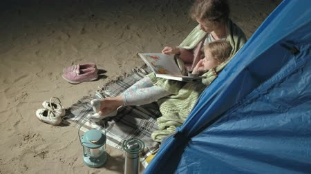 가까운 : Mother and her beautiful daughter read a book near a tourist tent at night on the beach