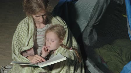 yakın : Mother and her beautiful daughter read a book near a tourist tent at night on the beach