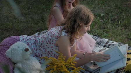 véu : A happy mother and daughter view photos in an album read a book. Family in a city park on a picnic on a warm evening at sunset.