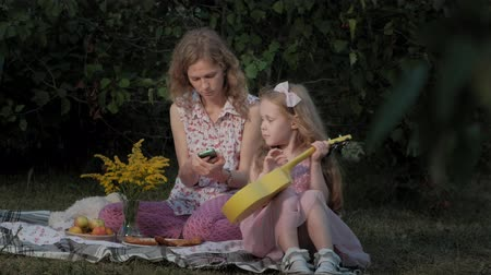 photo album : A happy mother and daughter are playing on the ukulele. Family in a city park on a picnic on a warm evening at sunset.