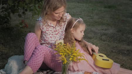 во : A happy mother and daughter are playing on the ukulele. Family in a city park on a picnic on a warm evening at sunset.