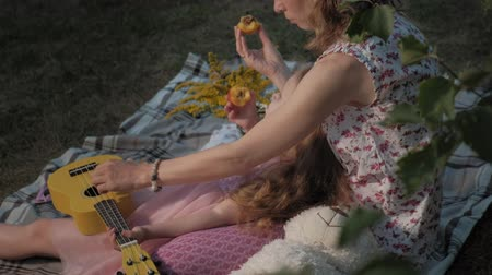 véu : A happy mother and daughter are playing on the ukulele. Family in a city park on a picnic on a warm evening at sunset.