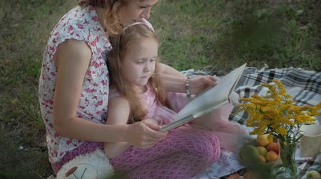 photo album : A happy mother and daughter view photos in an album read a book. Family in a city park on a picnic on a warm evening at sunset.