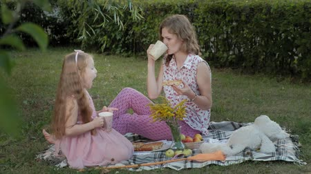 во : A happy mother and daughter are drinking tea on the veil. Family in a city park on a picnic on a warm evening at sunset.