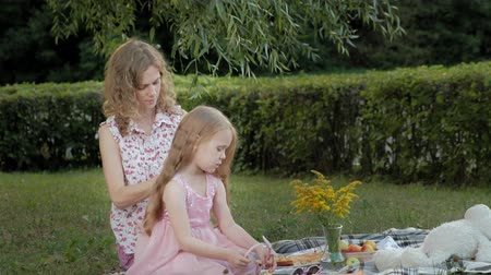 во : A happy mother combs her daughters hair. Family in a city park on a picnic on a warm evening at sunset.