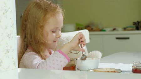 apetite : little girl eating porridge in the kitchen at home