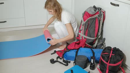 coisa : A woman tourist collects things in a backpack in the kitchen of the house and prepares for a trip