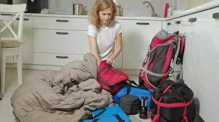 katolicismus : A woman tourist collects things in a backpack in the kitchen of the house and prepares for a trip