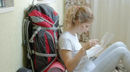 sırt çantasıyla : woman tourist collects things in a backpack in the kitchen of the house and prepares for the journey looks at the paper map