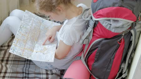 barok : woman tourist collects things in a backpack in the kitchen of the house and prepares for the journey looks at the paper map