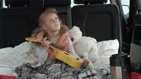 pień : Beautiful little girl sitting in an open trunk of a car on the river bank of the sea playing on a yellow ukulele