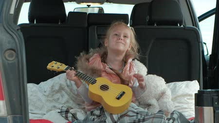 во : Beautiful little girl sitting in an open trunk of a car on the river bank of the sea playing on a yellow ukulele