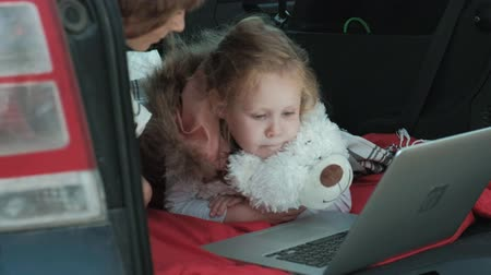 во : Beautiful young woman and her little daughter are sitting in the open trunk of a car on the river bank of the sea enjoying a laptop