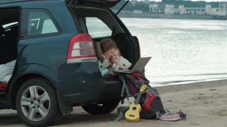 pień : Beautiful young woman and her little daughter are sitting in the open trunk of a car on the river bank of the sea enjoying a laptop