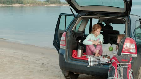 во : Beautiful young woman and her little daughter are sitting in the open trunk of a car on the bank of a river of the sea eating fruits and drinking tea from a thermos