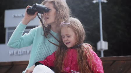 binocular : A woman with her daughter looking through binoculars on the beach