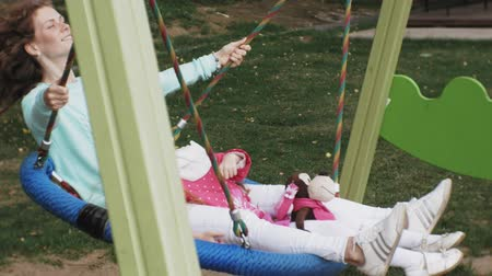 во : A little girl in a pink dress and her mother swinging on a round swing at the playground