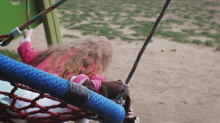 houpavý : A little girl in a pink dress and her mother swinging on a round swing at the playground