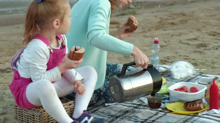 baharatlı alman sosisi : Mother and daughter fry meat and vegetables on a barbecue on the beach on the beach