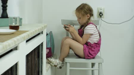 言うこと : little girl that sits at the chair, tries to playing a game with her smartphone. Child using mobile phone