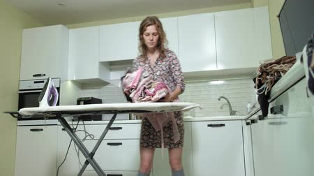 гладильный : woman ironing a mountain of laundry at home in the kitchen