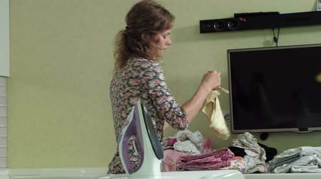 žehlení : woman ironing a mountain of laundry at home in the kitchen