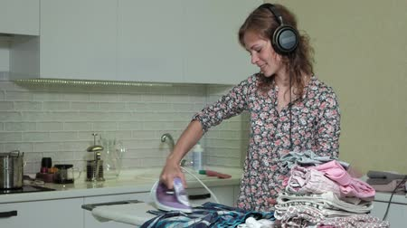 sprzataczka : woman ironing the mountain of laundry at home in the kitchen listening to music on headphones and dancing
