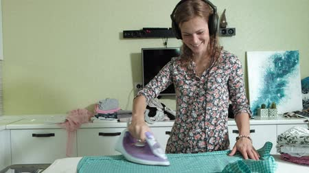 гладильный : woman ironing the mountain of laundry at home in the kitchen listening to music on headphones and dancing