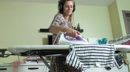 ütüleme : woman ironing the mountain of laundry at home in the kitchen listening to music on headphones and dancing