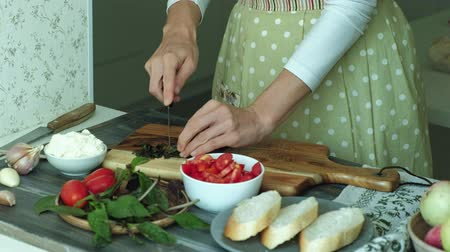 antipasti : Close-up shot of a womans hand is prepared from bread cheese and vegetables for an Italian bruschetta.