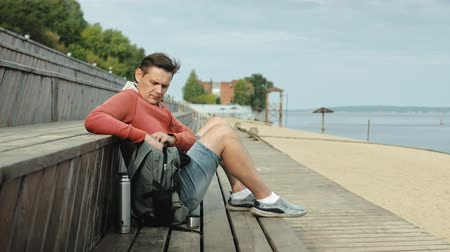 bank : Mature man, tourist using a laptop, sitting on the beach on a wooden bench