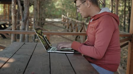 блог : Mature man is working on his laptop outdoors in nature during his vocation aged forester using his laptop for e-mail checking while sitting at huge wooden table