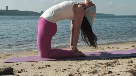 alguns : Old retired woman doing some yoga on the beach