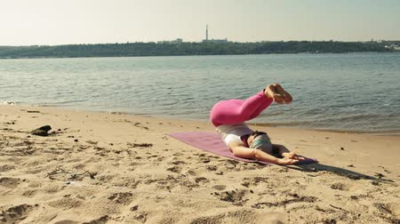 alguns : Old retired woman doing some yoga on the beach super slow motion