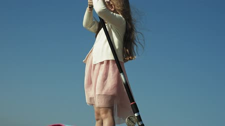fishing pole : Cute little girl is playing with a fishing rod on a fishing boat near the river