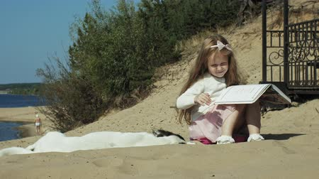 tahy : A sweet girl sits on the sand and reads a book strokes a dog