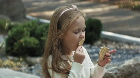 hair growth : A cute girl is sitting in the park and eating ice cream