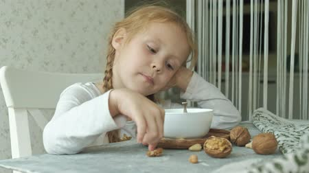 bonitinho : Little cute girl eats oatmeal with nuts and dried fruits for breakfast. Healthy food concept Stock Footage