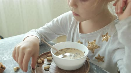 suszone owoce : Little cute girl eats oatmeal with nuts and dried fruits for breakfast. Healthy food concept Wideo